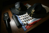 0074 State patrol hats lie on a chart with pictures and names of the state leaders next to metal...