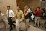 Frank Bingham, center with cheeks puffed, open neck yellow shirt, leaves a press conference, all...