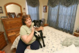 Susan Tatum and her black lab mix named Lucky in her bedroom of her duplex at 200 Cardinal Way,...