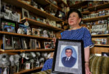 DLM0001  Surrounded by photographs representing a lifetime of memories and holding a photograph of...