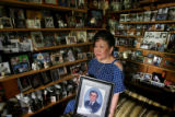 DLM0002  Surrounded by photographs representing a lifetime of memories and holding a photograph of...