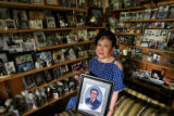 DLM0003  Surrounded by photographs representing a lifetime of memories and holding a photograph of...