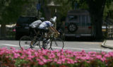 Two unidentified cyclists work out hard in the early afternoon heat at Washington Park in Denver,...