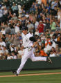 Rockies Brad Hawpe rounds the bases, as the crowd cheers his 3 run homer in the bottom of the...