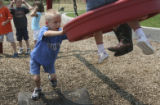 Aiden Chandler,6, gives his mates a ride on the swing in the playground between classes. (cq)....