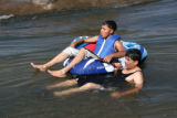 Luis Mondosa (cq), left, and Eliseo Juarez (cq) enjoy a raft ride on the South Platte River,...