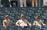 Rockies fans try to keep cool by going shirt-less as tempatures reached the high 90's as the...