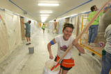 Katie Pace (cq) laughs while carrying a bucket of paint as she organizes a crew of volunteer...