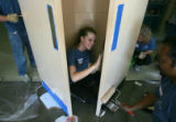 Andrea Baker (cq), 17, of Aurora, center, laughs while taping a door as she helps to paint a...