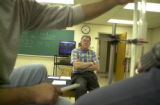 Physics professor Daniel Cohen watches as students work on a laboratory assignment that involves...