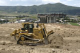 A D9 bulldozer moves some of the millions of tons of dirt on the headwall slope, a beginner slope,...