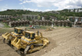 Several  D9 bulldozers move some of the millions of tons of dirt on the headwall slope, a beginner...