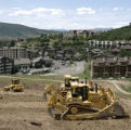 Bulldozers move some of the millions of tons of dirt on the headwall slope, a beginner slope, at...