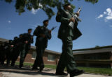 Members of the honor guard march past the Soldiers Memorial Chapel, after firing three shots for...