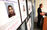 Denver PD Chief Whitman stands near photos of  suspects wanted for murderduring a press conference...
