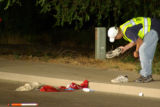 Grand Junction Officer Myles Shiflett examines a shoe of a man who was struck by a Hit & Run...