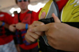NAAAP Team Member Leslie Moen (cq) of Arvada, Colo., fastens the buckles on her life vest before...
