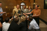 Frank Bingham, left center with open neck shirt, speaks with media outside  the courtroom with...