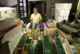 DLM3975  Ed Barraclough, the new operator of the Rocky Mountain Seed Company, stacks boxes filled...