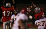 Rocky Mountain quarterback, Alex Kelly, #5, squeezes a pass through two Heritage defenders, Friday...