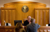 Visiting Judge Joseph Weatherby (cq) talks with Defense Attorney Maria Liu (cq, left) and...