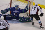 EPD CAPTION CORRECTION  provides IDs : Vancouver Canucks' Roberto Luongo, left, makes a save on a...