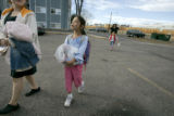 0085 Janae Cashman, 8, CQ, center, carries a bag of food she received through the Feeding the...