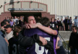 Two of the kids that David Rossiter coached hug his brother , back to camera, Pete Rossiter...