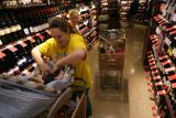 Stephanie Herrera (cq)of Castle Rock, adjust her son Jayden clothing in the wine section with with...