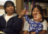 Esther Avelar sits next to her daughter, 11-year-old Araceli Gimenez who is holding 1-year-old...