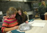 Aide Donna Fitzgerald (cq), left, helps Megan Bomgaars (cq), 14, right, with her art assignment at...