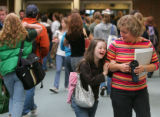 Megan Bomgaars (cq), 14, smiles as she walks arm-in-arm through school with her aide Donna...