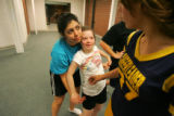 Natalia Portillo (cq), left, hugs Megan Bomgaars (cq), left, while talking with fellow cheerleader...
