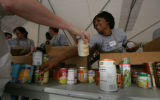 Shyanne Robinson (cq) and other members of the DNCC help sort donated food into boxes at the...