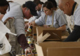 Members of the DNCC help sort donated food into boxes at the Crossing in Denver, Colo. on Friday,...