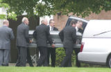 Pall-bearers load the first casket into a hearse at the conclusion of the Post family funeral at...