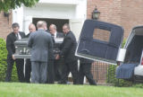 Pall-bearers load the second casket into a hearse at the conclusion of the Post family funeral at...