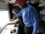Jim Sullivan, of Big Jim's Ribs mobil van in Parker, helps Jerry Dominquez put together a couple...