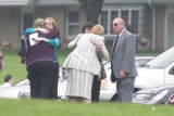 Mourners hug in the parking lot of the Grace United Methodist Church in Wyckoff, N.J. after...