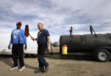 Jim Sullivan, of Big Jim's Ribs mobil van in Parker, talks with his employee Jerry Dominquez, who...