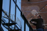 Ryan Glasspoole, cq of Larimer Square hangs a portion of Larimer Squares's light canopy featuring...