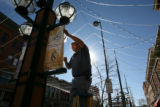 Larry McKenzie, cq of Larimer Square hangs banners up Larimer Squares's light canopy, which...