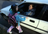 Kitana Aragon, 5, left, says goodbye to her mother Jessica Walters after being dropped off outside...