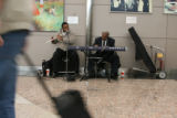 Musicians Vince Wiggens and Joe Bonner, cq, of the Wiggens - Bonner Duo, plays for passengers and...