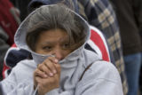 DM0166   Gloria Morales, 49, tries to keep warm as she waits in line to receive a Thanksgiving...