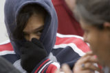 DM0306   Rose Morales, 39, left, covers her face from the cold wind as she and her sister Gloria...