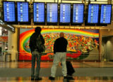 Travelers check departure times  at Denver International Airport   early Wednesday morning...
