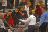 Travelers pass through security screening at Denver International Airport  with less than a ten...
