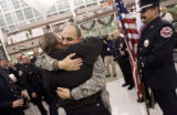DM0712   Sgt. Jens Pietrzyk, 27, right, gets a hug from Chaplain Bob Paige as he is greeted by...
