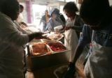Volunteers spend their Thanksgiving , giving,  by volunteering to prepare Thanksgiving meals to...